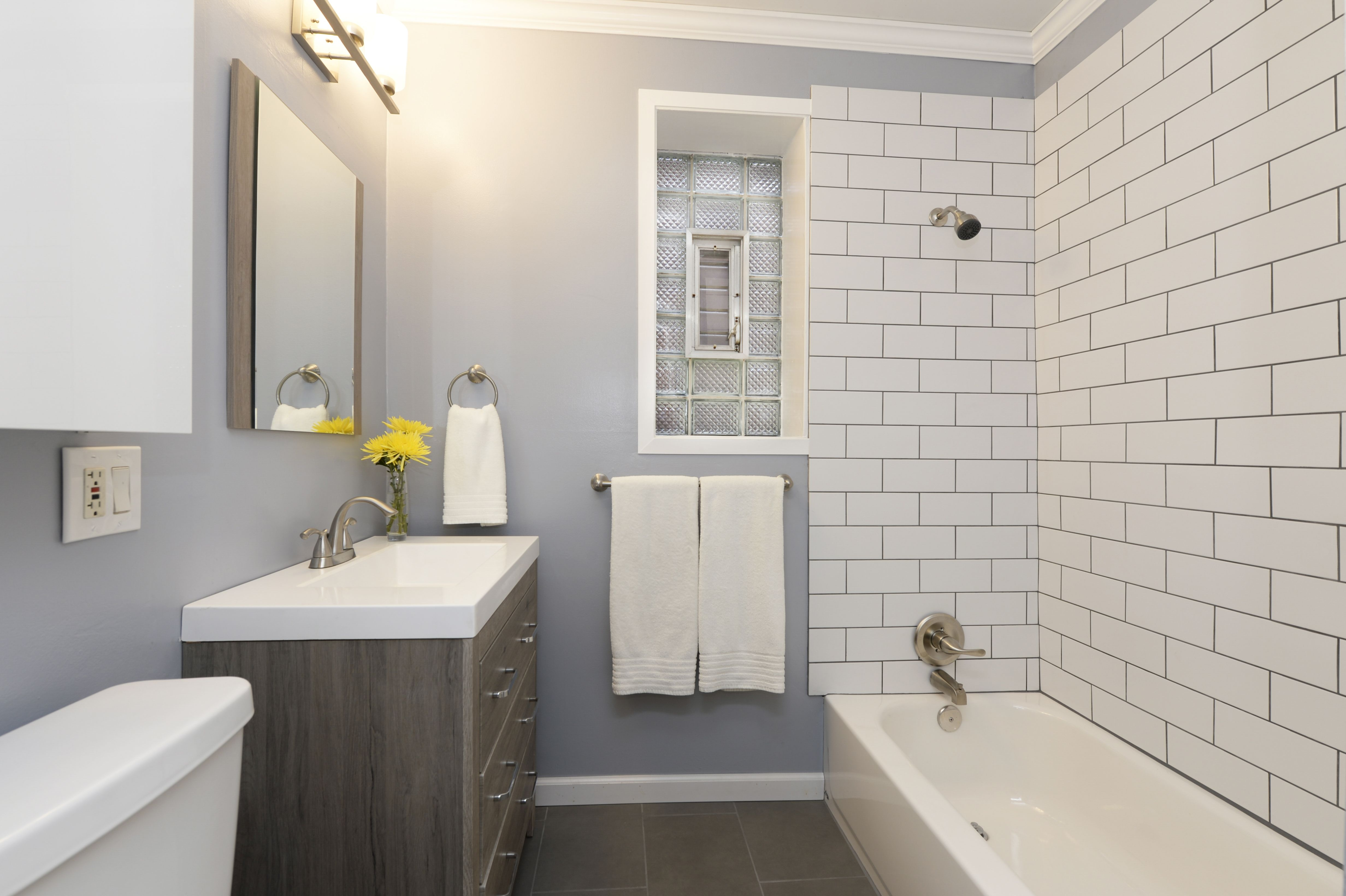 The Bathroom Rehab At This Vintage Apartment Added White Subway Tile And Floating Wooden Vanity With Apartment Bathroom Grey Bathrooms Small Apartment Bathroom