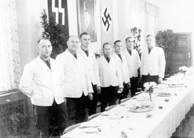 Stutthof, Poland, A group of waiters, next to set tables, in the officers' dining room.
