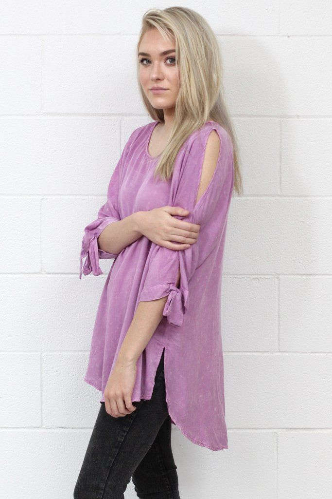 Mineral washed perfection tunic top! The sleeves are a favorite with their bows and cut out details! They can also be tied in a knot and left more loose instead of a bow. Sides have slits. Slight high-low cut. Loose fitting. Mauve / purple color.