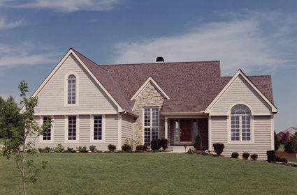 Multiple gables, a covered porch, and circle-topped windows combine to enhance the attractiveness of this exciting home.  House Plan # 161034.