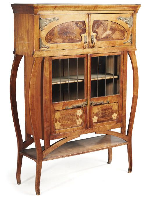 A MARQUETRY DISPLAY CABINET   the shaped form with turned panelled doors inlaid with the head of a maiden, above glazed and panelled doors enclosing shelves, with Art Nouveau brass handles and pulls, signed C Spindler