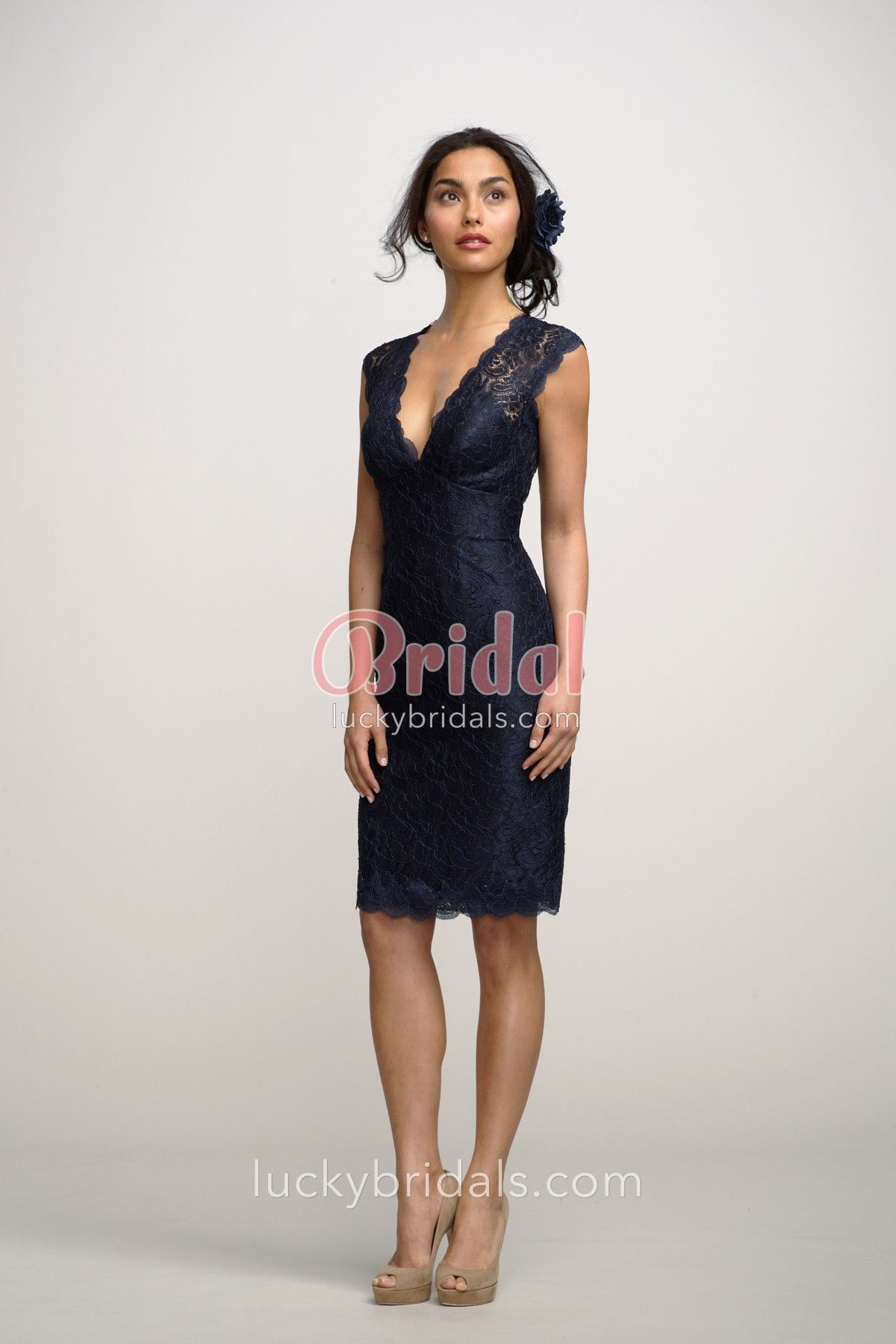 88f1ef7c182bc Navy lace plunging V-neck short bridesmaid dress over black lining with cap  sleeves, above the knee length skirt and open keyhole back.