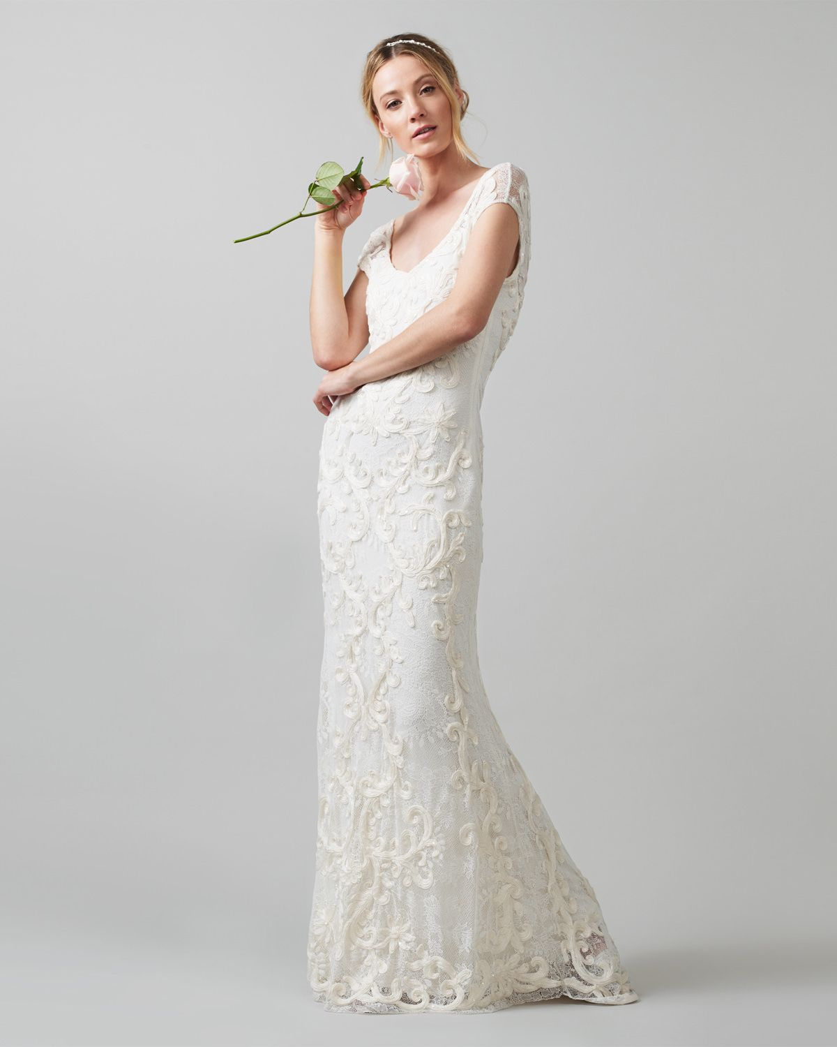 A striking full length wedding gown with swirling tapework on a lace ...