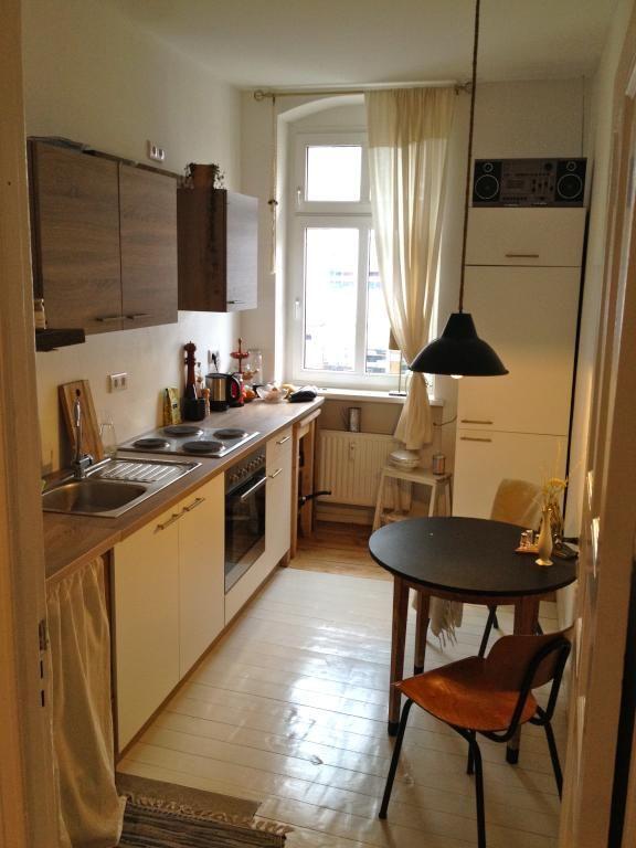 Gemütliche Kücheneinrichtung mit Dielenboden, hohem Fenster und ...