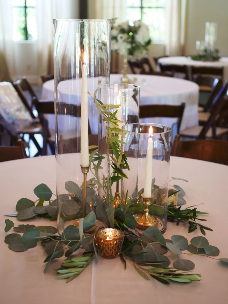 Tapered Candles With Brass Accents And Natural Greenery Around The Base Wh Pretty Wedding Centerpieces Wedding Floral Centerpieces Wedding Table Centerpieces