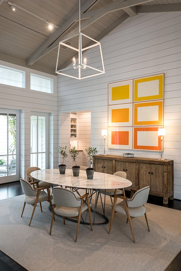 Dining room design with white shiplap walls and a oval marble dining