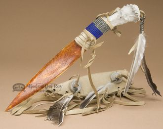 This is a decorative Native American hand made Navajo knife and sheath for dance or display. The knife handle is genuine antler and the blade is made of bone. The knife sheath is crafted from distress
