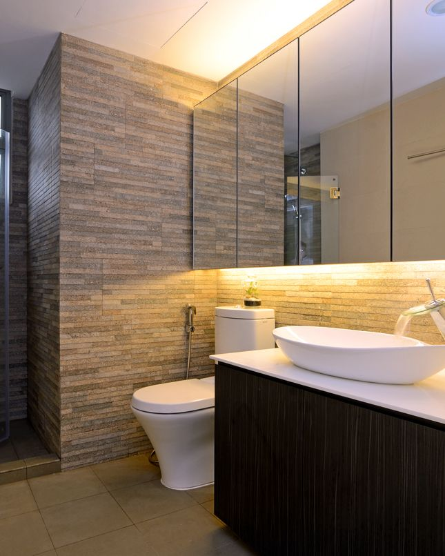 elegant indian crib bathroom interior with stone tiled backsplash brightened by under cabinet lighting