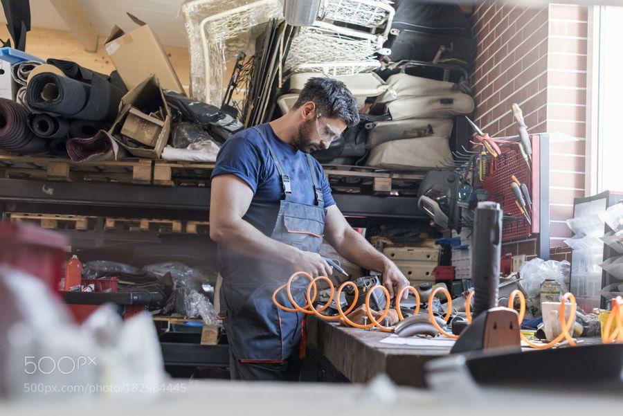 Mechanic using equipment at workbench in auto repair shop