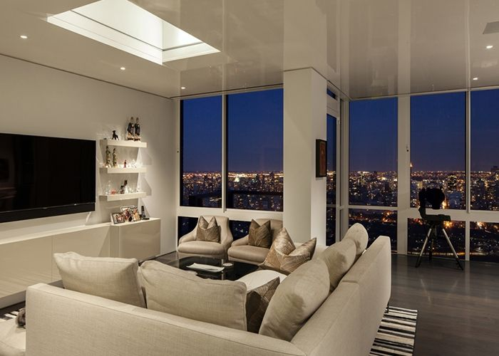 View of the living room at night with the bright lights of for New york penthouse apartments
