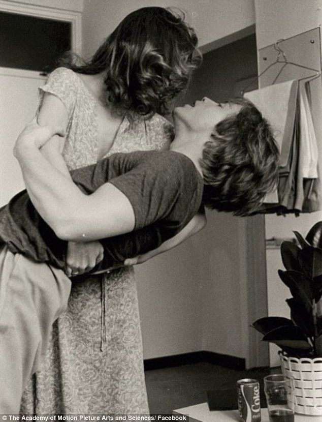 Goofing around: Carrie and Mark are dancing in one of the photos, which have been put up for auction by Carrie's mother Debbie Reynolds  damn those guns