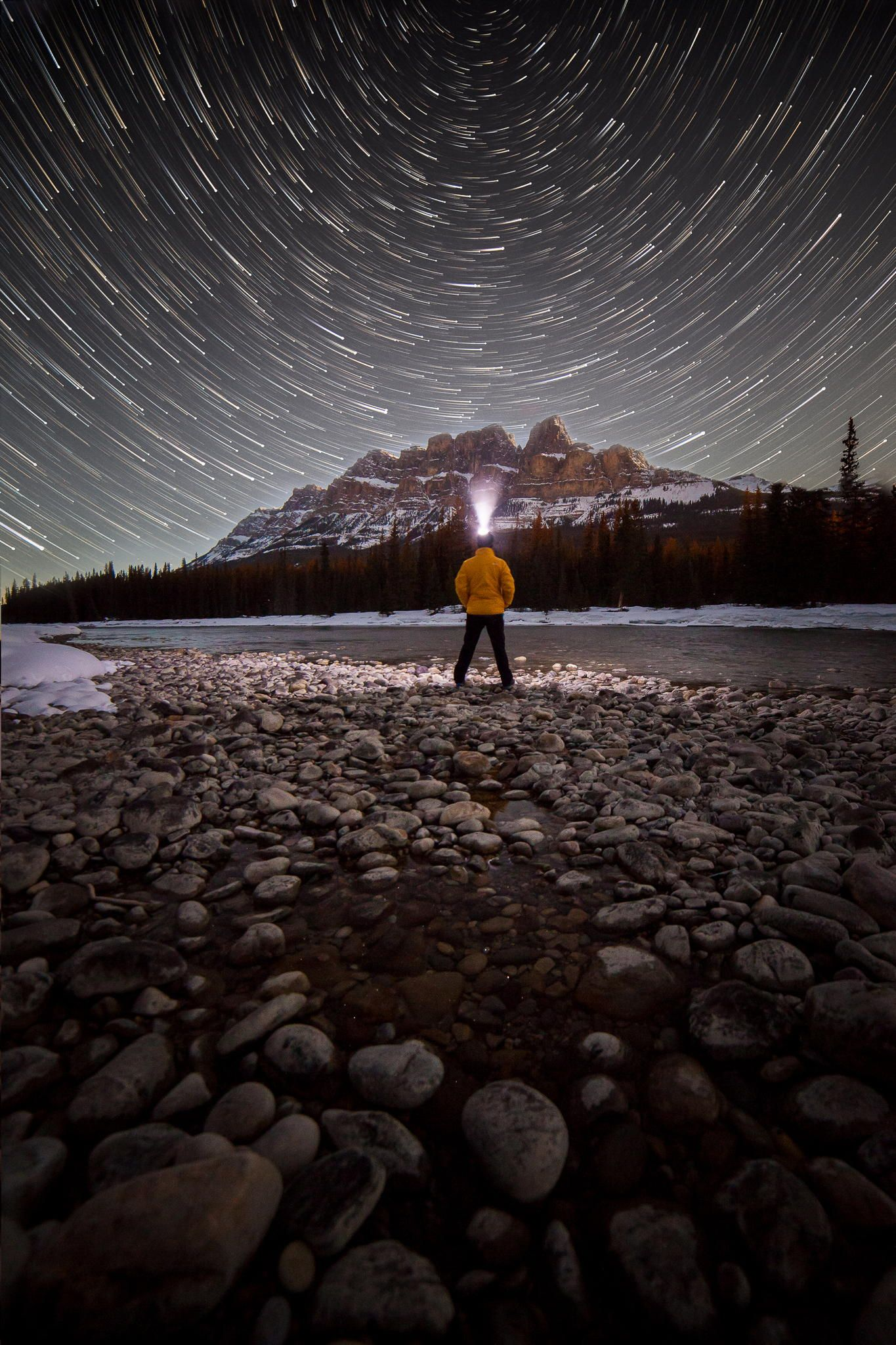 The hairs on my nostrils freezing with every inhale, the lapping of the water along the shores of the Bow river in front, the rustle in the bushes behind making a Chipmunk sound as big as a Bear; a beautifully chilling night under the stars.   Captured along the shores of the Bow River in Banff National Park in Spring. 91 photographs created this scene to create the star trails.