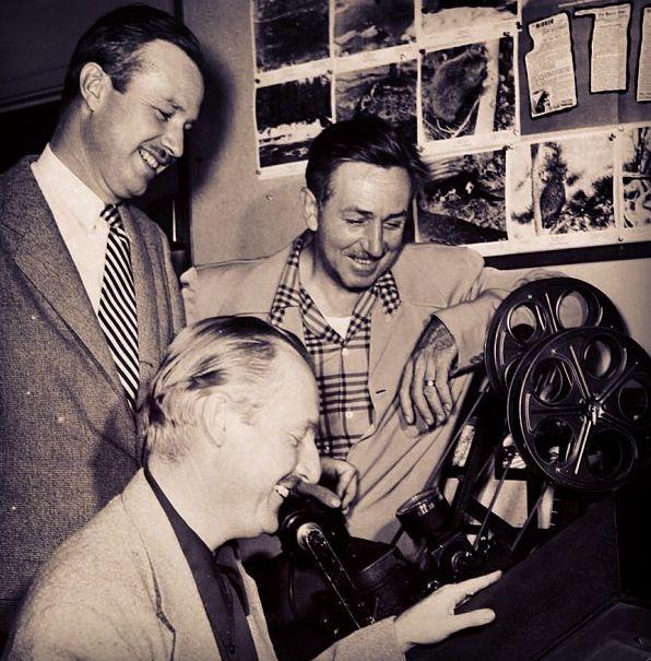 Walt Disney & friends looking over a film.