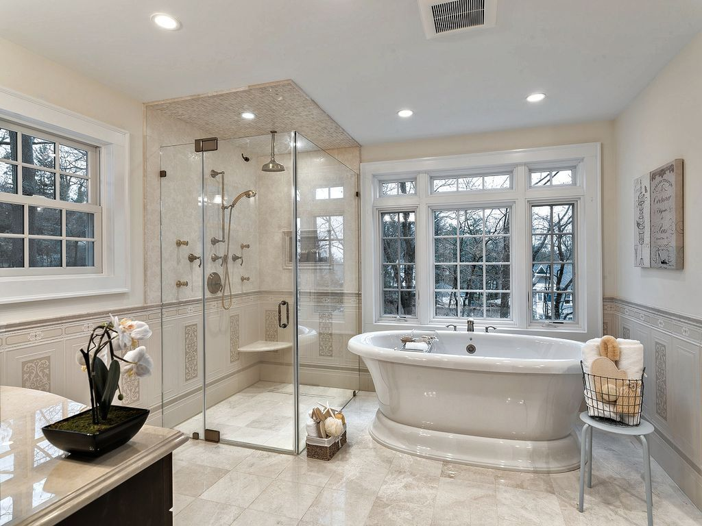 traditional master bathroom with freestanding bathtub handheld shower head frameless showerdoor limestone counters