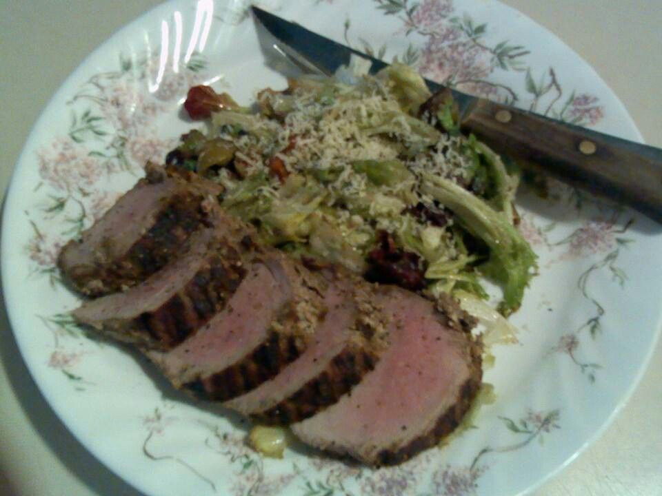 Grilled pork tenderloin with baby green wilted salad with vingerette.