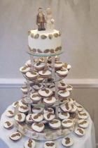 Wedding cup cakes with groom and bride toppers picture