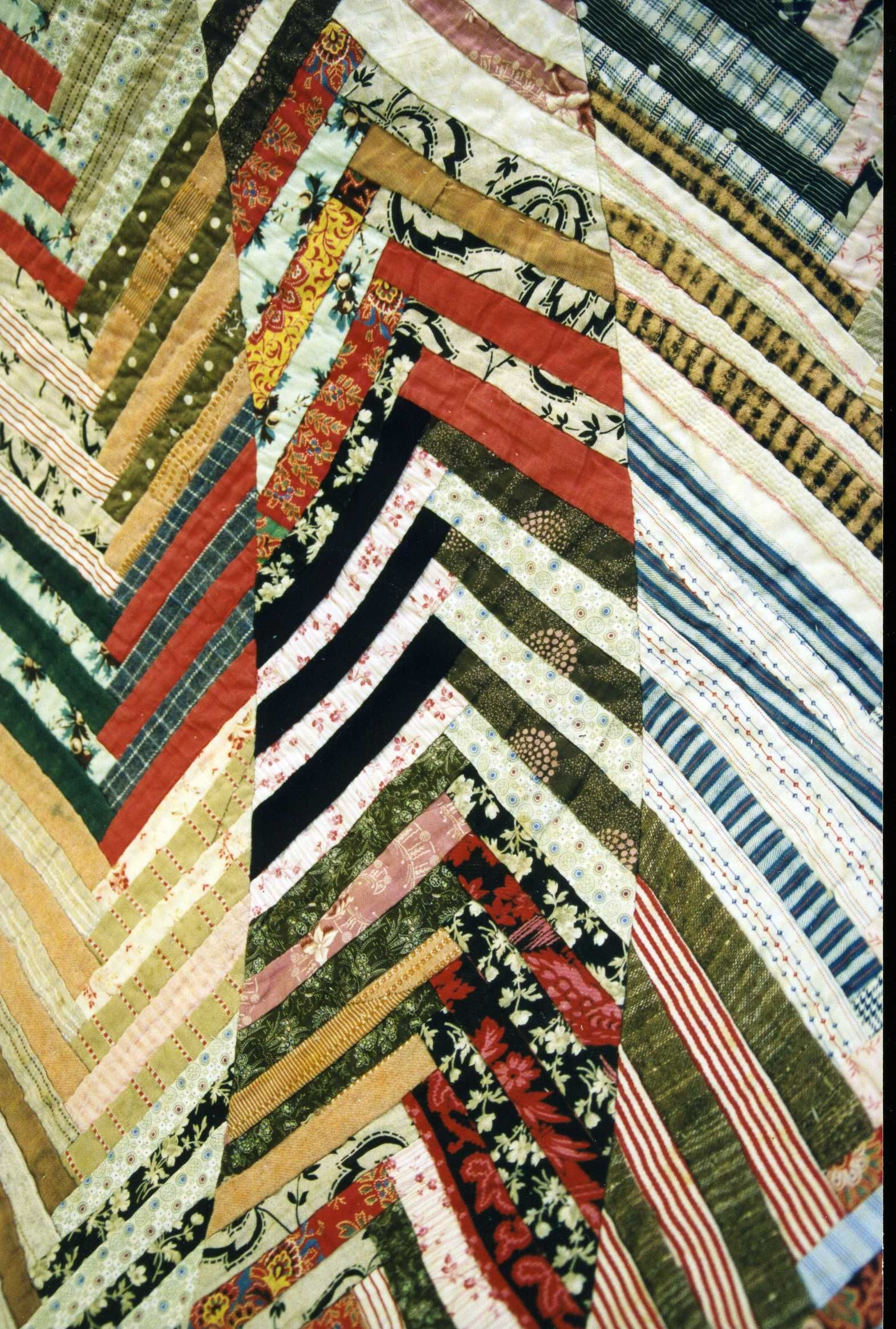 c.1880 - 1900 A colourful cotton and wool strippy Chevron quilt, hand quilted and hand and machine sewn. Strips of fabric pieced in 'V's in log cabin style to make long lengths. The lengths were then joined together to create a zig-zag effect across the quilt. Quilted in straight zig-zag and diagonal lines.
