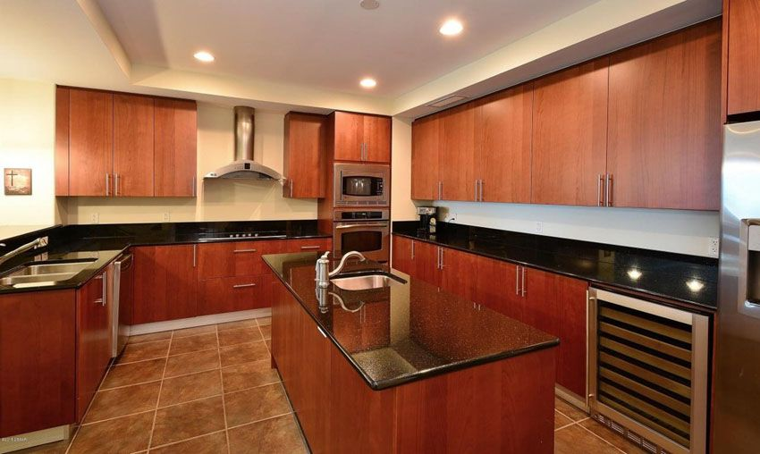 Superbe Modern Kitchen With Cherry Cabinets, Black Granite Counter Tops, Wine  Fridge And Rectangular Island With Undermount Sink.