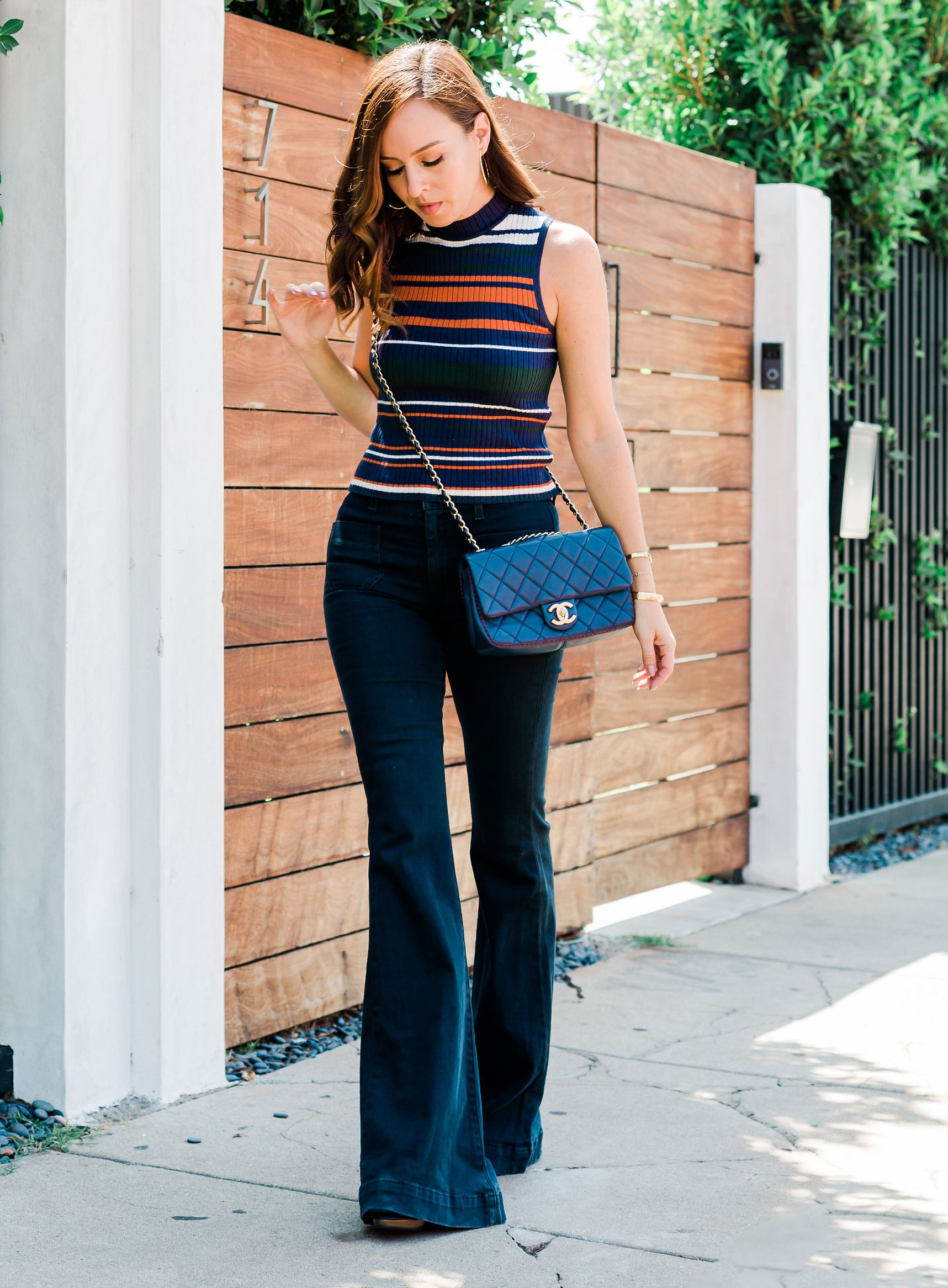 b99c88590e Sydne Style shows how to wear sleeveless turtlenecks for fall with wide leg  jeans  stripes  turtleneck  chanel