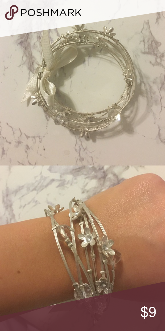 Francesca's bangles! Set of silver bangles tied together with a bow. They have flowers and clear accent beads on them! Worn a few times Francesca's Collections Jewelry Bracelets