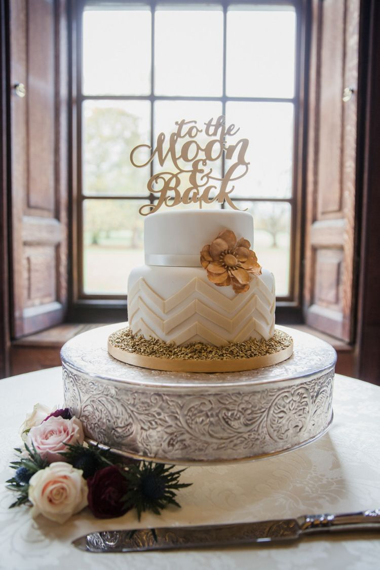 Two tier white cake decorated with gold flower and cake topper   Photography by http://www.kerryannduffy.com/