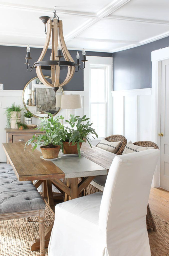 Dining Room {2019}   Gorgeous dining room area with navy blue walls, white batten board, wooden chandelier, farmhouse dining able, neutral rug, and greenery. #diningroom #diningroomideas #farmhousediningroom
