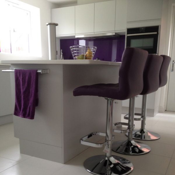 Malmo matt light grey handle-less kitchen with with porcelain tiles, white quartz and feature glass splashback.