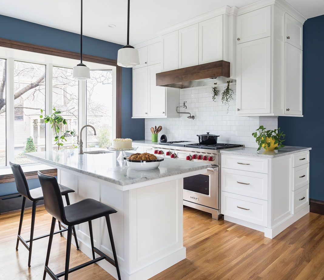 A Kitchen With Wood Flooring White Cabinetry Stainless Steel Appliances And A Blue Accent Wall Classic White Kitchen Kitchen Remodel Kitchen Remodel Small
