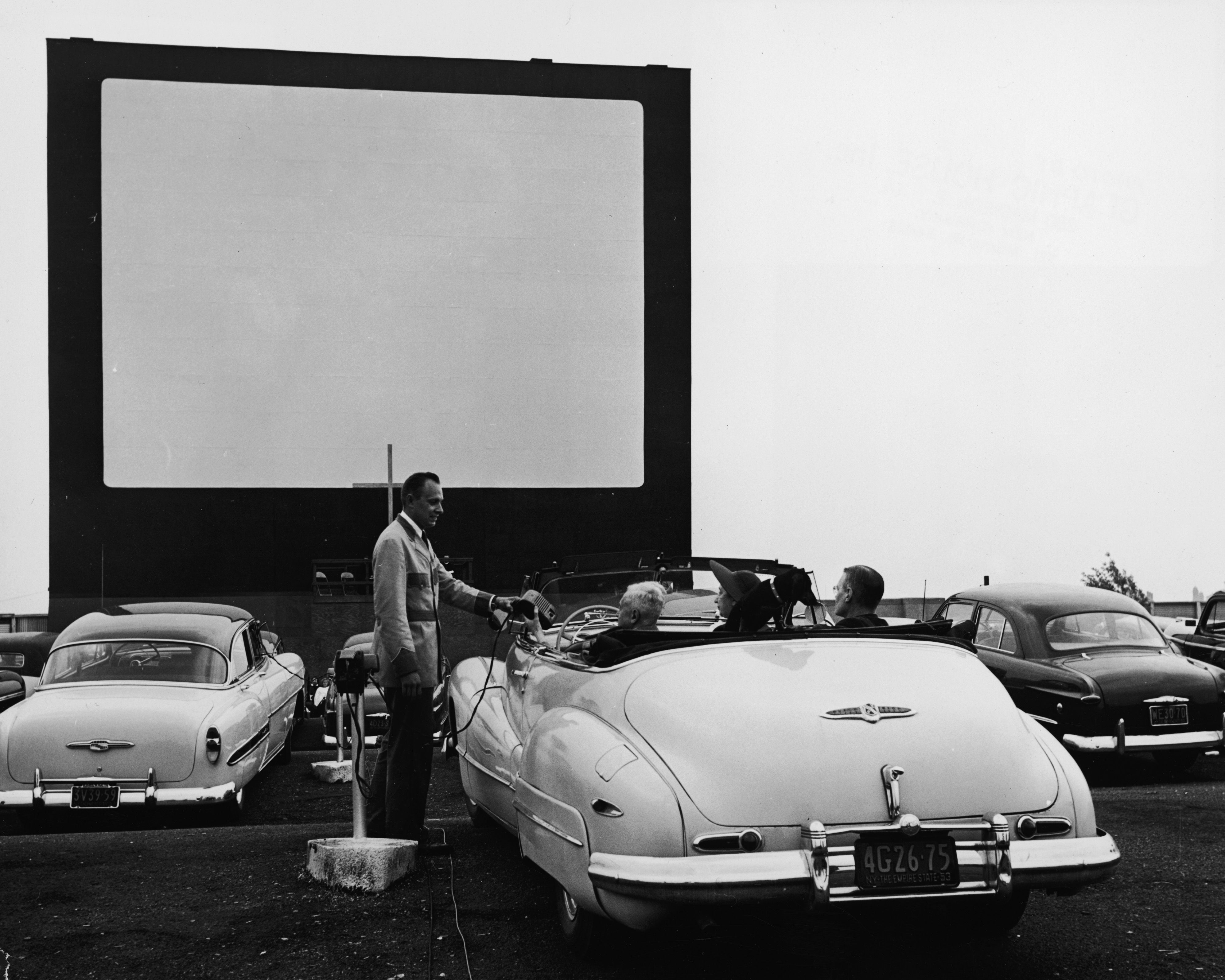 A Uniformed Drive In Theater Attendant Hands A Clip On Speaker To The Driver Of Convertible While The Ca Drive In Movie Theater Drive In Movie Drive In Theater