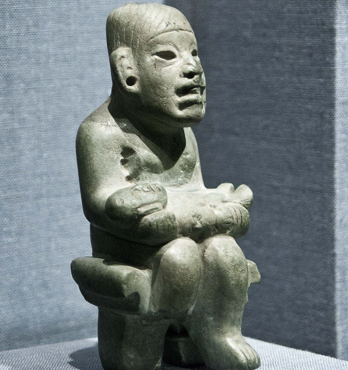 Seated figure holding infant