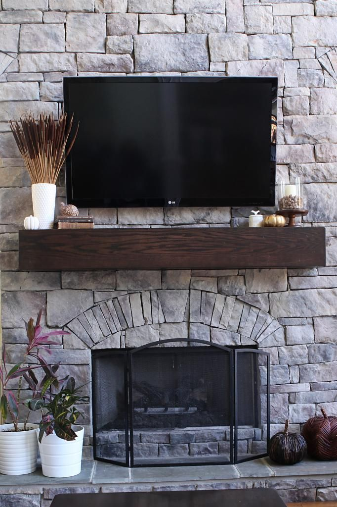 wood mantle stone fireplace built ins around fireplace TV above