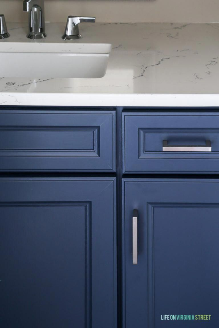 Powder bathroom cabinets freshly painted in a cool navy blue, Delta Faucet faucet, Behr Castle Path Walls and Benjamin Moore Hale Navy Cabinets. Love the fresh, nautical vibe! Countertops are Daltile One Quartz in the Luminesce color. #bathroomcabinet #halenavybenjaminmoore
