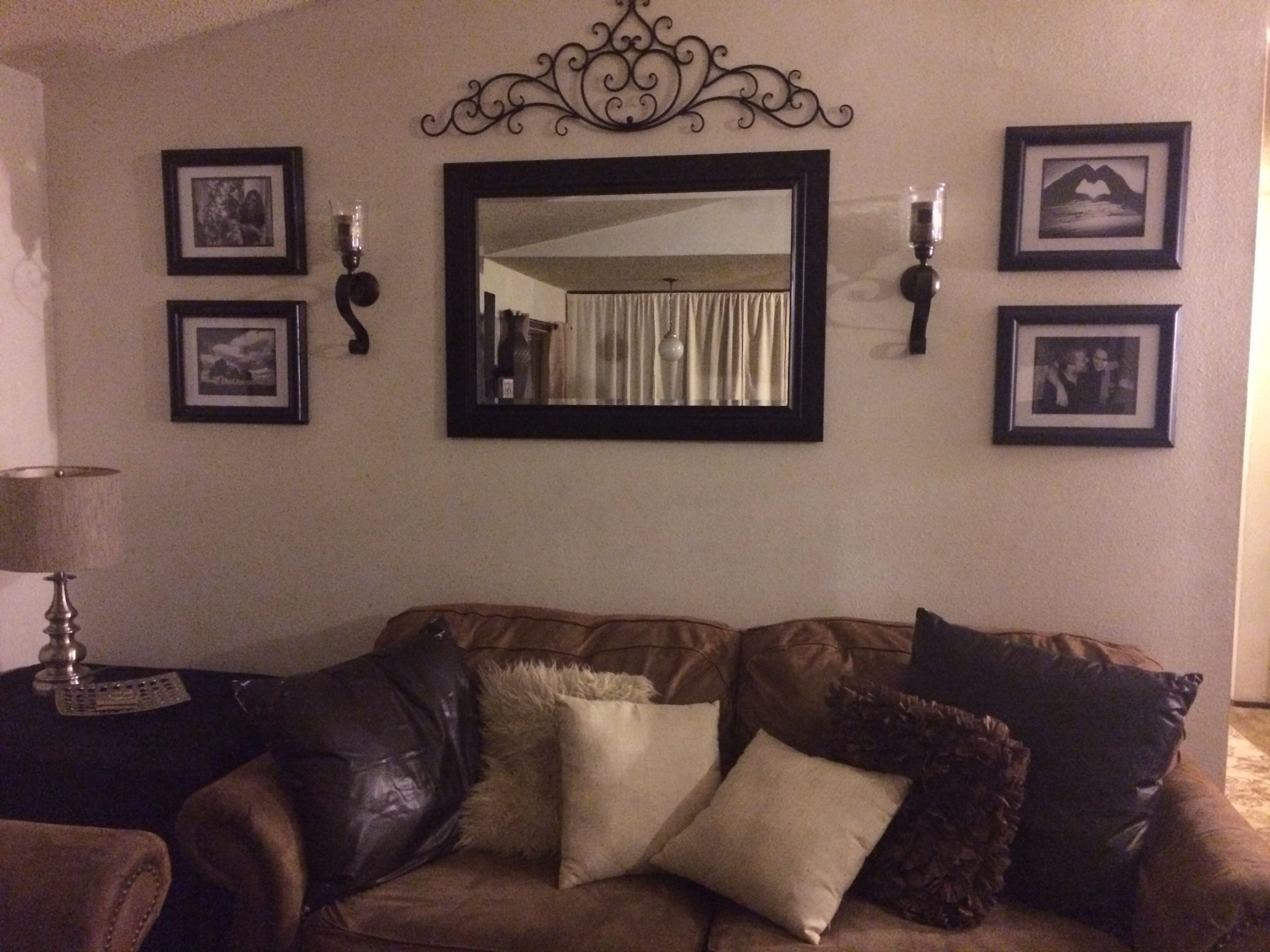 behind couch wall in living room mirror, frame, sconces, and metal