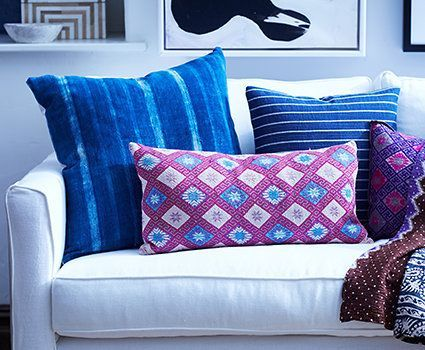Pile on the Prints: Colorful pillows and throws can instantly make over a room—and take a white slipcovered sofa from basic to beautiful. Don't hesitate to mix patterns from far-flung  locales; just stick to one or two color families (like the cool blues and purples here) to keep the look cohesive. Global Allure | One Kings Lane