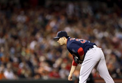 Boston Red Sox relief pitcher Junichi Tazawa, of Japan, prepares to throw to the Baltimore Orioles in the seventh inning of a baseball game,...