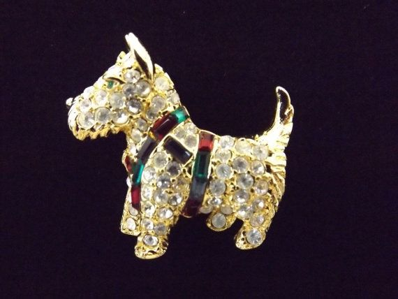 This adorable Scottie dog pin was designed by Kenneth Jay Lane. It is beautifully done in a gold tone metal with bright shiny faceted crystals and colorful accent stones. There is even a green stone for the dogs eye. The pin measures 1-1/2 wide and 1-1/4 tall. Im a dog person so this pin caught my eye right away. Whether you own a dog or not, this is such a fun piece of jewelry to wear. It will definitely be a great conversation piece whether you wear it for work or play. It would also make…