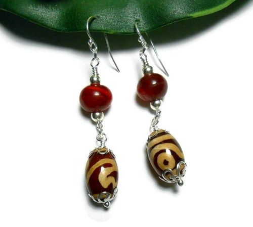Handmade beaded earrings. These earrings are a long length of 2.5 inches including the wires. They have been created with dark rust red barrel lamp work beads with golden tan painted designs. I have a