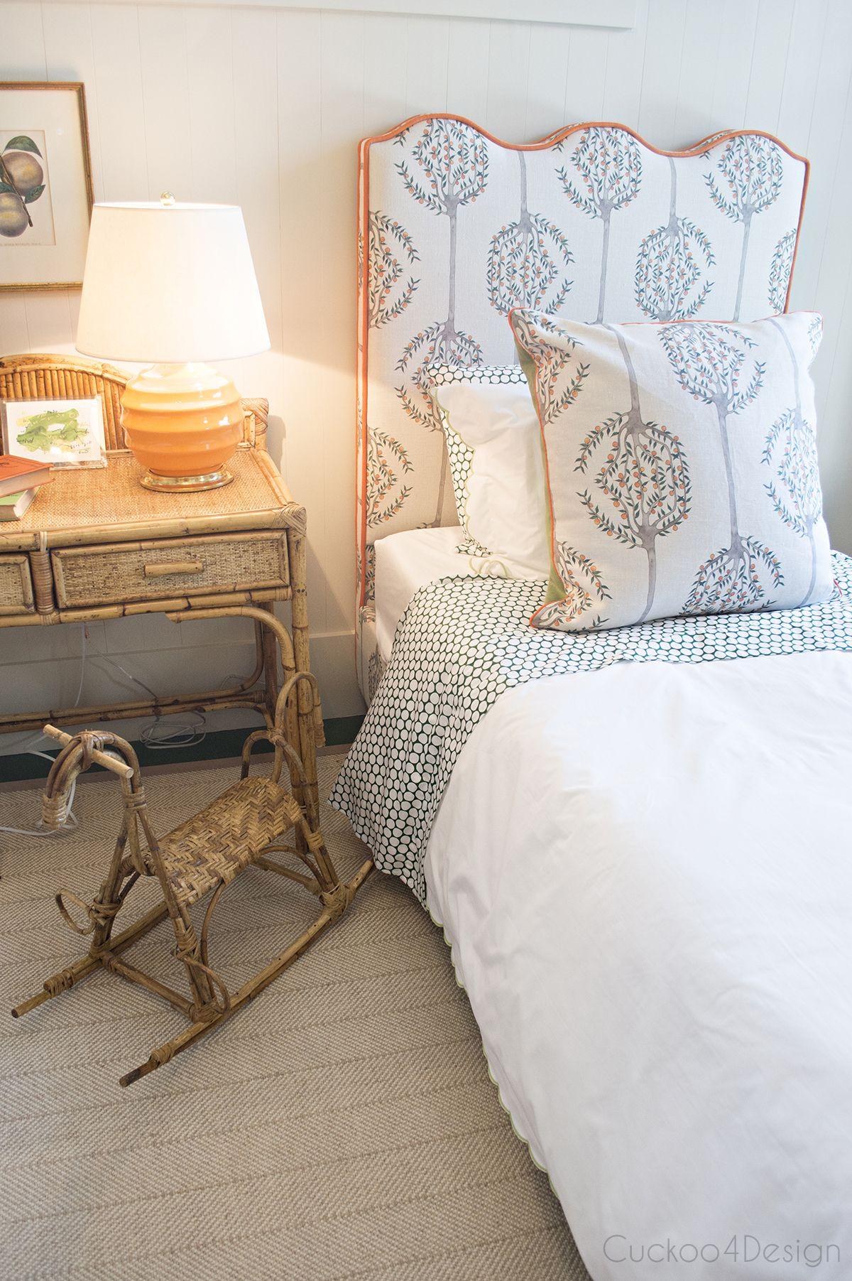Kids bedroom with upholstered headboard orange trim and vintage wicker furniture