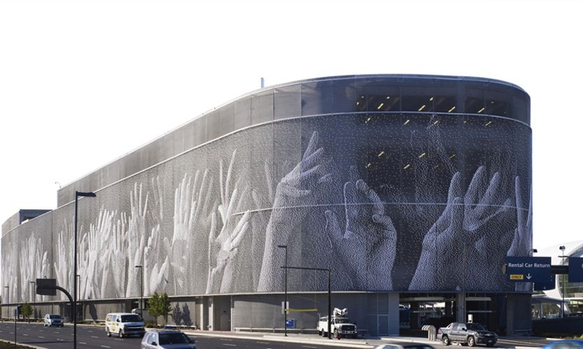 Hands an iconic mural on the faade of San Jose International Airports new parking garage was