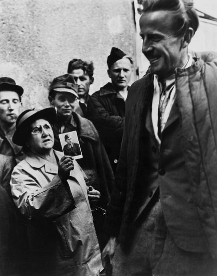 A mother shows a picture of her son to a returning POWs. Vienna. 1947. Photograph by Ernst Haas.