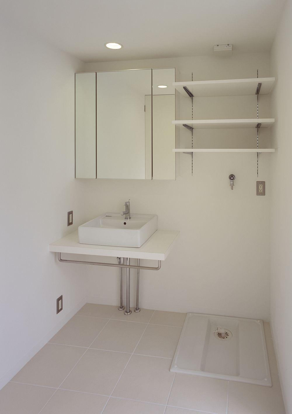 バスルームと同じ白い床タイルを使用した コンパクトにまとめた洗面所