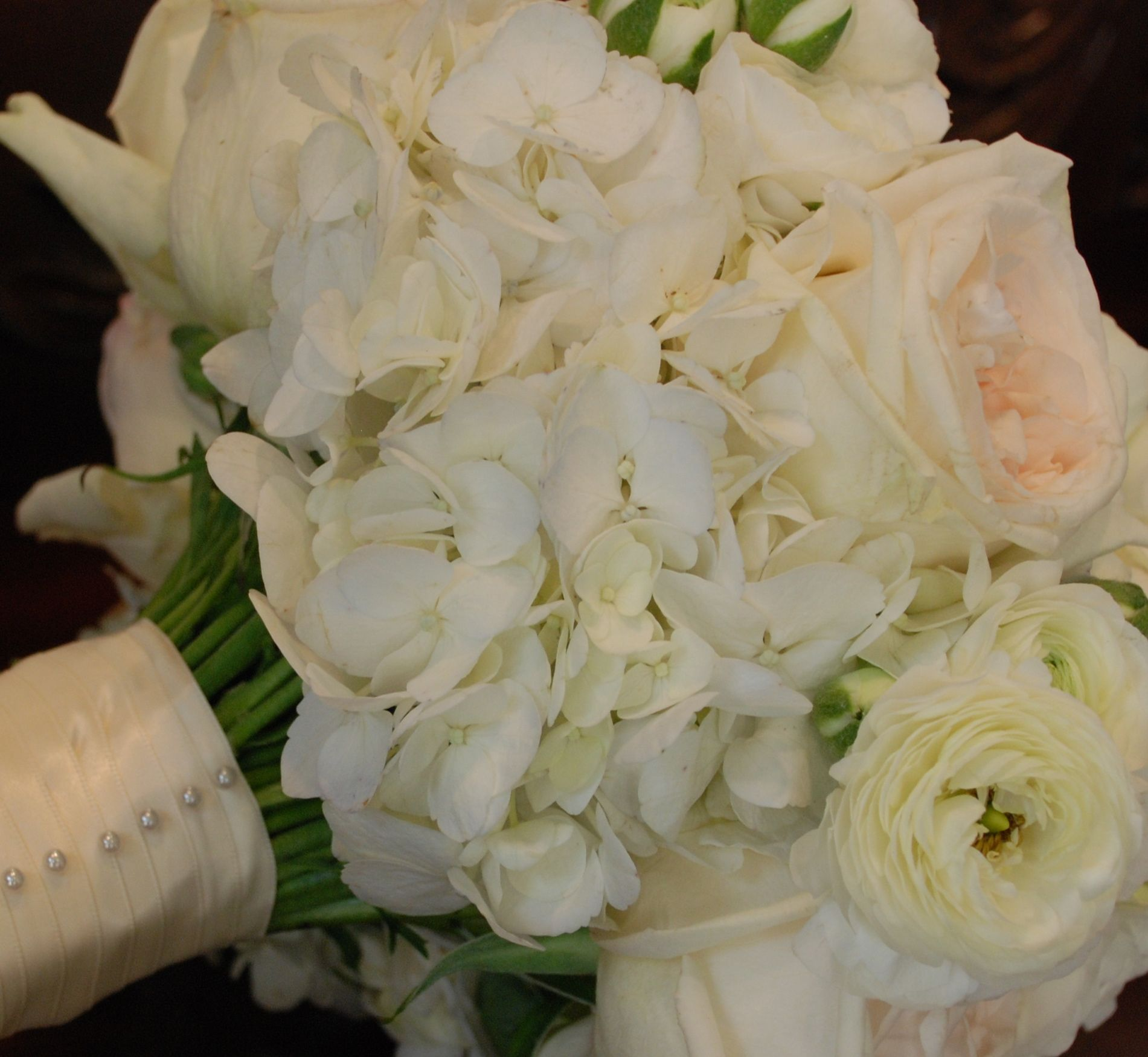 bridal bouquet of white ohara garden roses white ranunculus white hydrangea wrapped