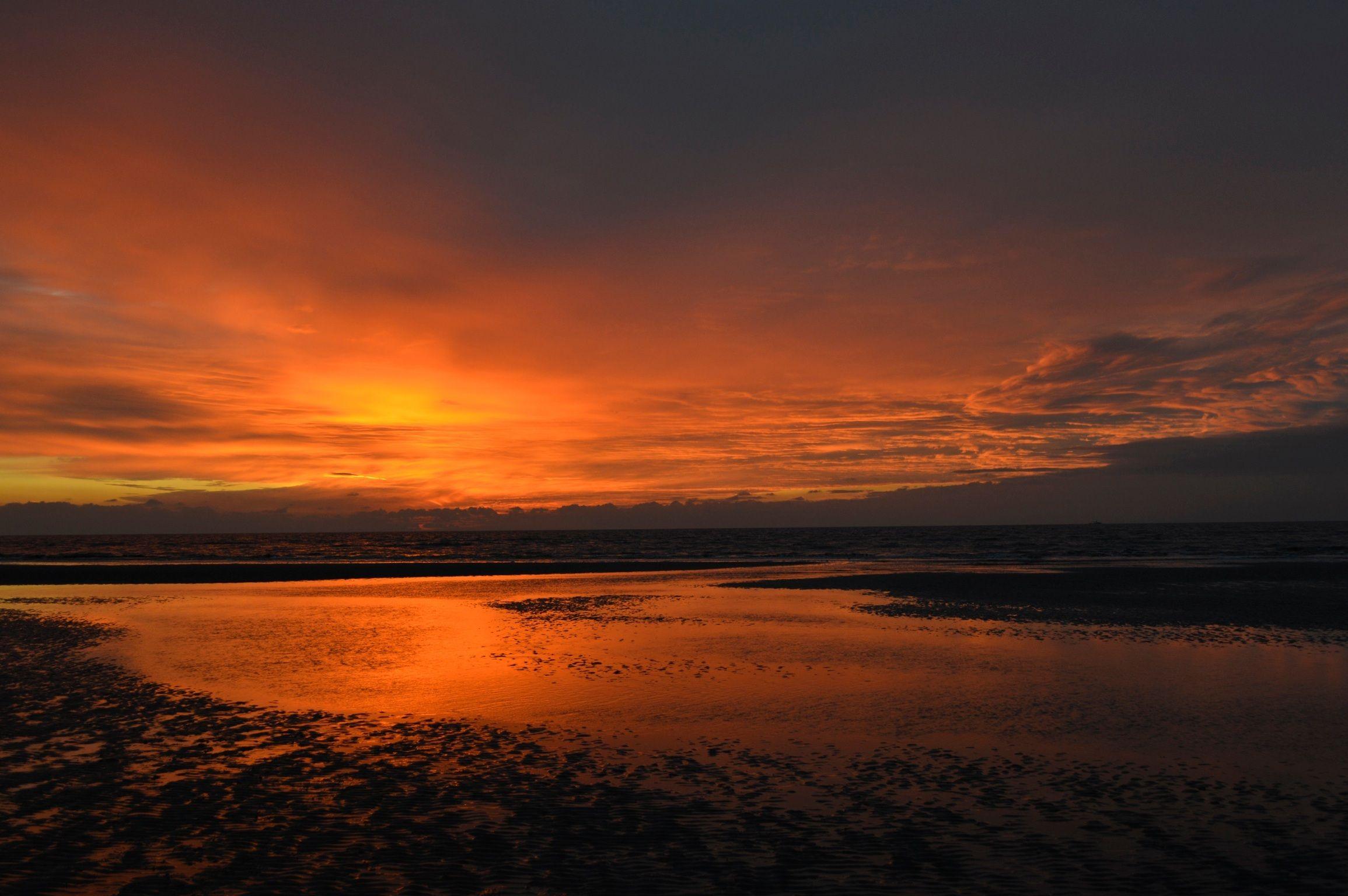 Solnedgång med spegling i havet.