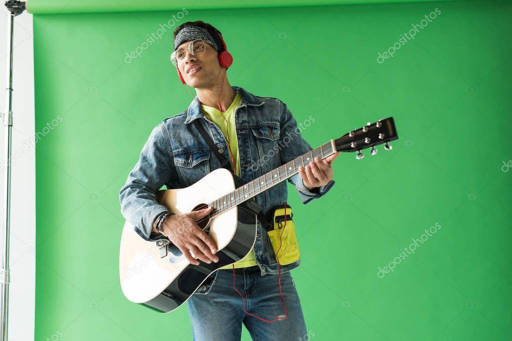 Handsome Mixed Race Man Denim Headphones Playing Acoustic Guitar Green Stock Pic Aff Man Denim Headphones Handsome Acoustic Guitar Acoustic Guitar