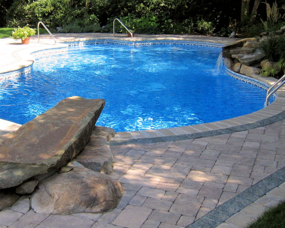 Pool with dive rock water fall and detailed paving design for Stone swimming pool