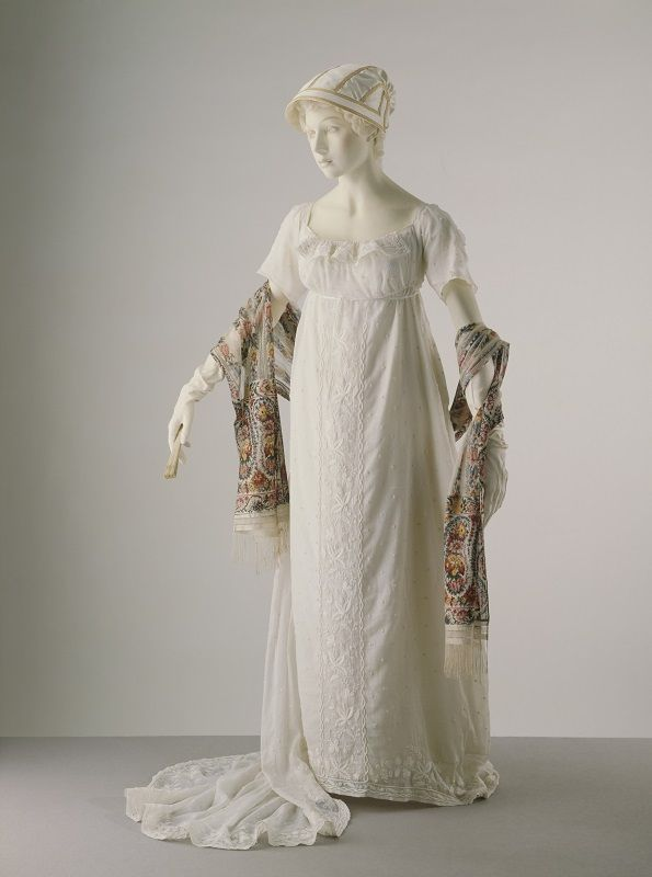1806 ca.  Evening Dress, French. White muslin, embroidered all over in white cotton. 1810 ca. Scarf, printed knitted silk,English.  19th Century Early. Fan, carved and pierced ivory, English.