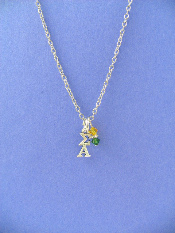 Celebrate your sorority with this fashionable necklace featuring your letters and sorority colors! Officially Licensed.  17 inch chain sorority necklace features a sterling silver plated Greek letter Sigma Alpha lavaliere (1/4Wx 5/8L) and an maize and green 4mm Swarovski crystal bead dangle. Chain and lobster clasp are both base metal alloy. Perfect gift for sorority initiation, Bigs and Littles, new pledges, holidays and birthdays, or just because! Additional quantities are availab...