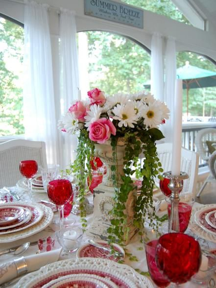 Red, white and pink aren't just reserved for Valentine's Day dinners. To create this romantic Old World centerpiece, arrange pink roses and white daisies, and surround them with homegrown creeping Jenny in a rustic urn. For a touch of intimacy and elegance, add silver candlesticks on either side of the arrangement. Design by Susan Herin of Between Naps on the Porch.