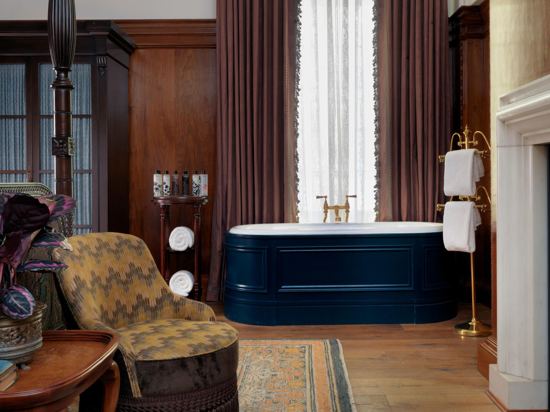 Wooden panelled bathtub painted dark blue in one of the