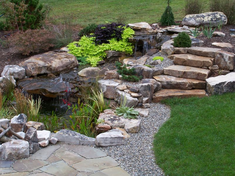 Water feature boulder fire pit and stone slab steps for Koi pond next to pool